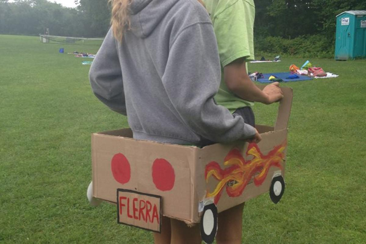 Two People Riding in a Cardboard Flerra Vehicle